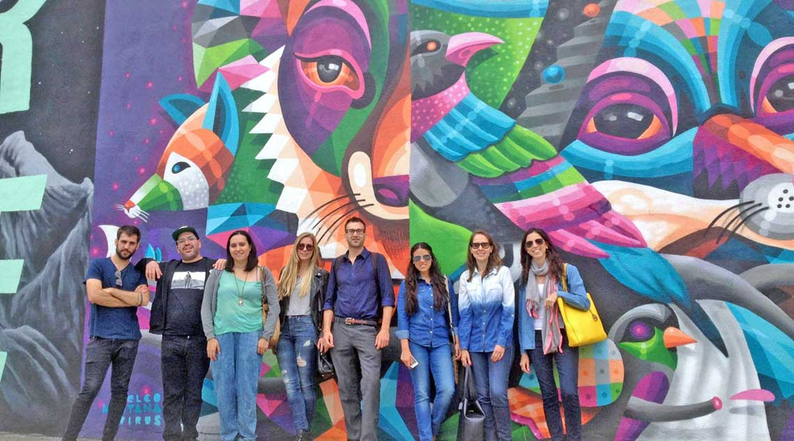 Tour group stands in front of artwork in Bushwick, Brooklyn.