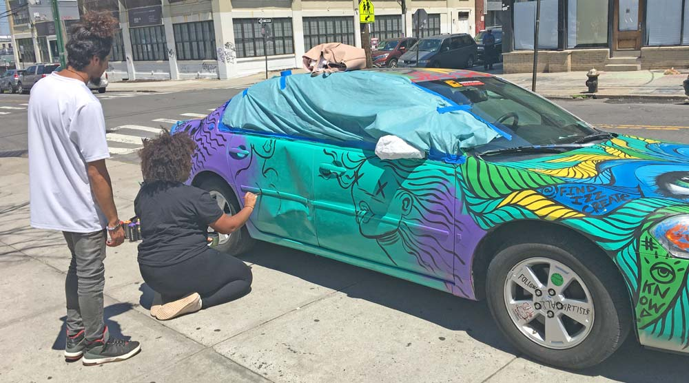 Artist painting on car