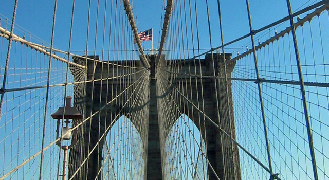 american flag flying on brooklyn bridge tower