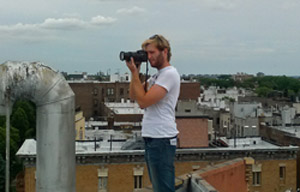 man on roof taking photo