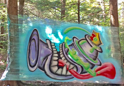 painted artwork on canvas in forest